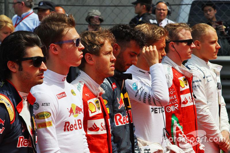 Daniil Kvyat, Red Bull Racing and Sebastian Vettel, Ferrari as the grid observes the national anthem