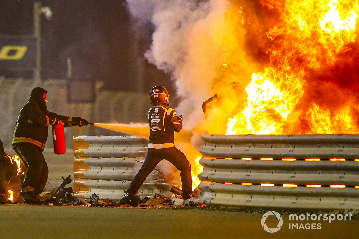 Los bomberos se encargan de las llamas y un delegado médico saca a Romain Grosjean, Haas F1 del monoplaza