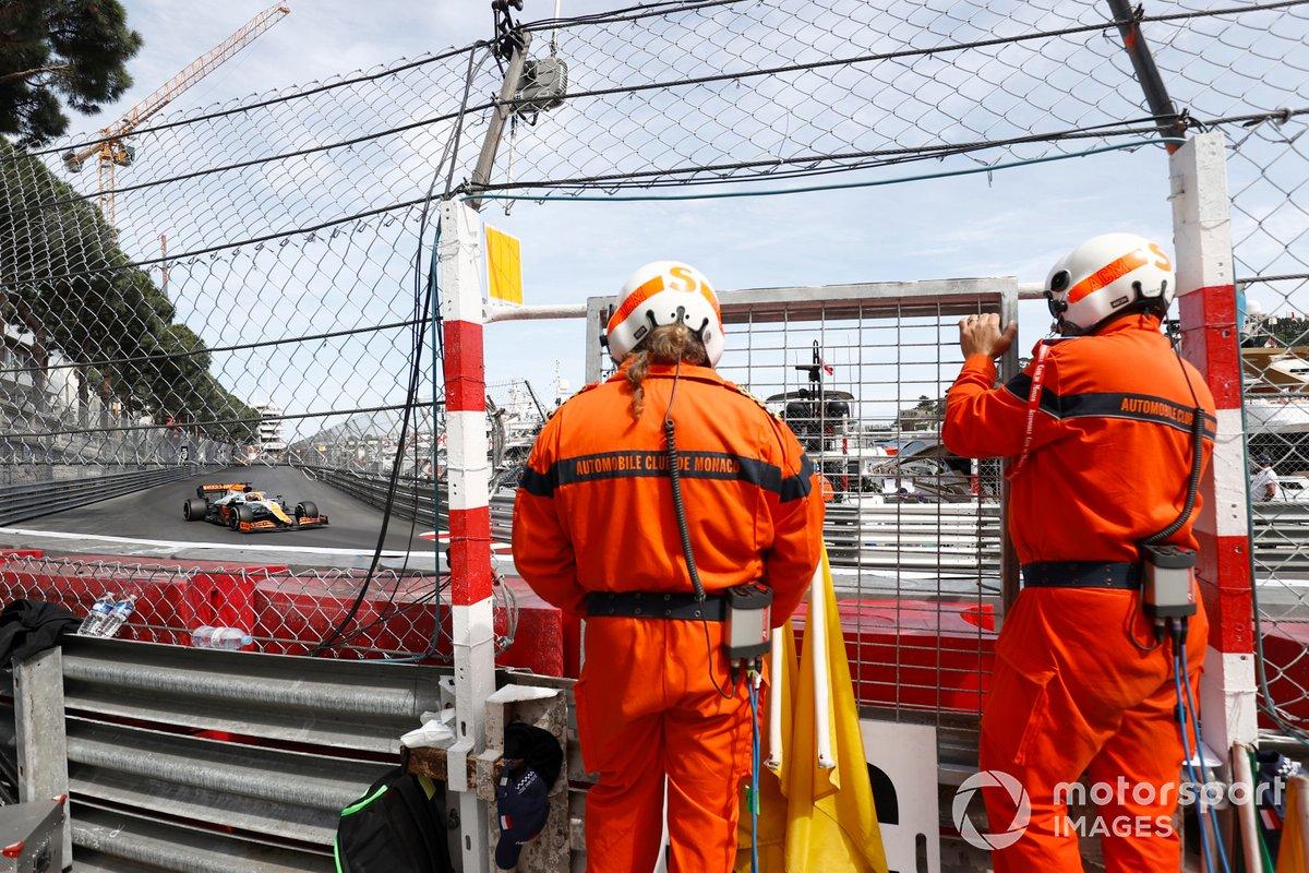 Marshals watch as Daniel Ricciardo, McLaren MCL35M, passes