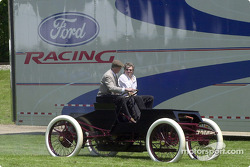 Glenn Miller, development engineer at Ford Special Vehicle Engineering, and John Force, ten-time Funny Car champion, cruise around the activities field in a Ford 1901 Sweepstakes replica