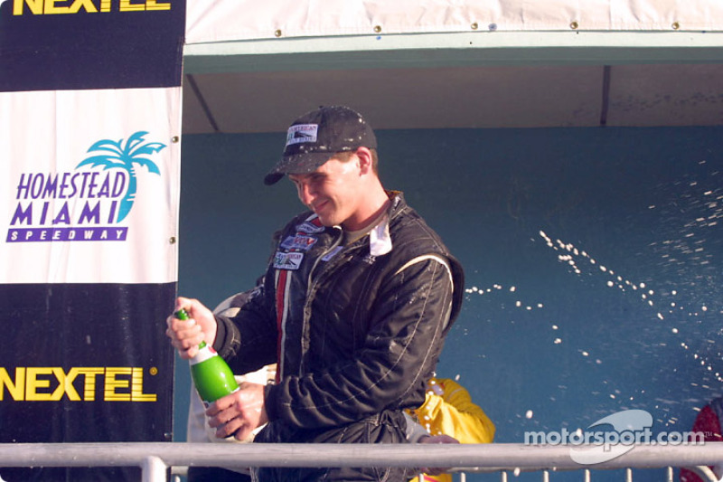 Andy Lally sprays champagne during the victory circle celebration on the podium at Homestead-Miami Speedway