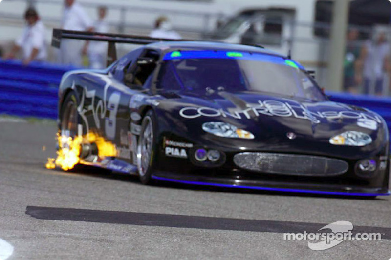 The #3 Jaguar backfires flame as it races through the infield