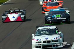 The #9 BMW M3 leads a pack of cars down a stort straight during practice