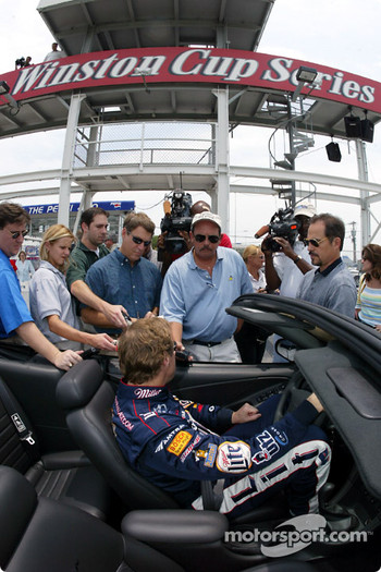 Rusty Wallace sits behind the wheel of the Rolex Sports Car Series pace car while giving interviews to the media about the upcoming Pepsi 400 and Jani-King Paul Revere 250