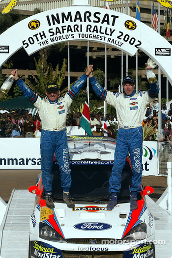 Colin McRae and co-driver Nicky Grist celebrating victory
