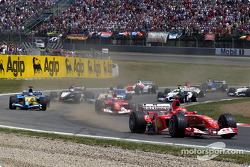 First corner: Michael Schumacher ahead of Fernando Alonso and Rubens Barrichello