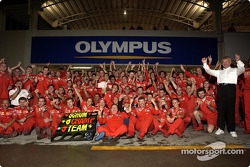 Michael Schumacher and Rubens Barrichello celebrate with Ferrari team members