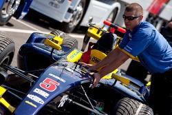 A Super Nova Racing mechanic pushes Josef Kral Super Nova Racing car into the paddock