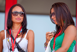 Two girls above the pit lane watch the action