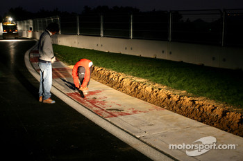 People working on the last corner curbs, turn 18