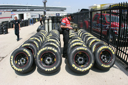 Crew member for Tony Stewart checks tire pressures