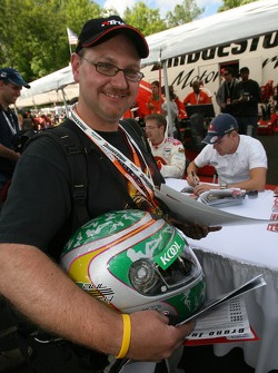 A happy fan with a Paul Tracy helmet