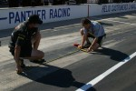 Team Panther crew members mark the pit lane with colored tape