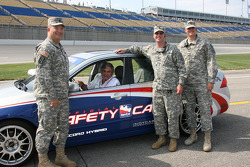 Fans pose before riding in the pace car