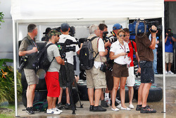 The media shelter from the rain in the paddock
