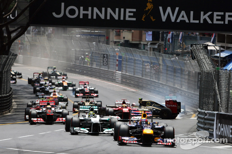 Mark Webber, Red Bull Racing leads at the start of the race as Romain Grosjean, Lotus F1 crashes