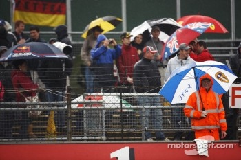 Fans and marshals brave the rain in the grandstands
