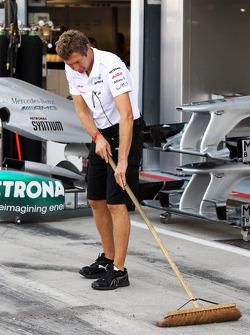 Mercedes AMG F1 mechanic sweeps the pit lane