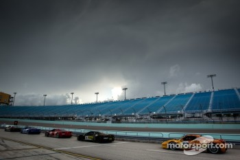 Cars lineup on pitlane under menacing sky