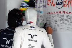 Bruno Senna, Williams takes a look at messages of suppport on a banner in the pit garage