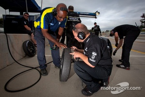 Michelin and Nissan DeltaWing technicians check a front tire of the #0 Nissan DeltaWing