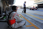 McLaren mechanic watches Fernando Alonso, Ferrari pass in the pits