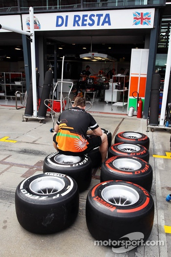 Sahara Force India F1 Team mechanic marks Pirelli tyres outside the pit garages