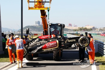 The Lotus F1 E21 of Kimi Raikkonen, Lotus F1 Team is recovered back to the pits on the back of a truck after he crashed in the first practice session
