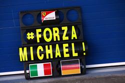 Een Ferrari pitbord met een steunbetuiging aan het adres van Michael Schumacher