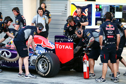 Red Bull Racing mechanic with an extinguisher at the rear of the Red Bull Racing RB10 of Daniel Ricciardo