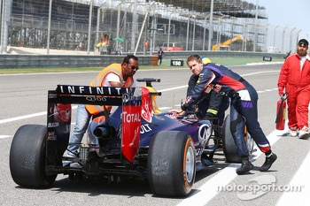 Sebastian Vettel, helps return his Red Bull Racing RB10 back to the pits after stopping at the pit exit