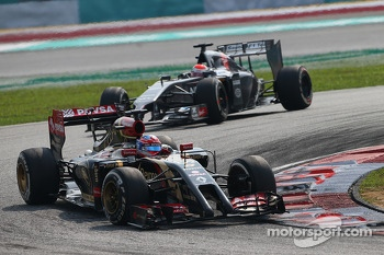Romain Grosjean, Lotus F1 E22 leads Adrian Sutil, Sauber C33