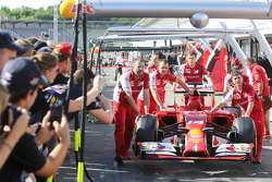 Fans in the pits as the Ferrari F14-T is pushed down the pit lane