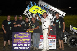 Isaac Schreurs celebrates in victory lane with his father and team
