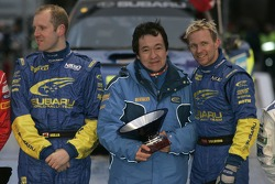 Winners Petter Solberg and Phil Mills celebrate with Subaru's Toshi Azuma