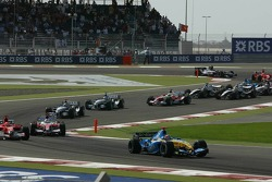 First corner: Fernando Alonso leads while Michael Schumacher and Jarno Trulli battle