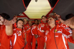 Ferrari team members watch qualifying