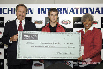 Mike Searles, CEO of Wilson Leathers, presents a ten thousand dollar donation to Kasey Kahne and Ernestine Sanders, president of Cornerstone Schools