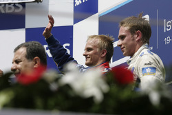 Podium: race winner Heikki Kovalainen with Adam Carroll