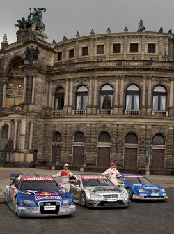 Rinaldo Capello and Stefan Mücke pose with DTM cars in front of the Semper Opera in Dresden
