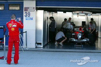 A Ferrari team member takes a picture of the MF1 Racing garage