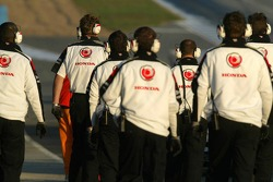 Honda team members walk to pit exit