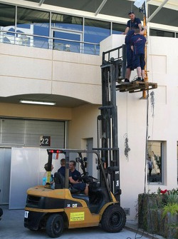 Red Bull Racing team members set up their radio and data mast