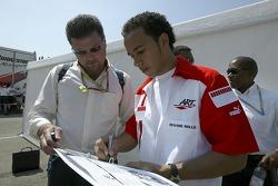 Lewis Hamilton signs his autograph