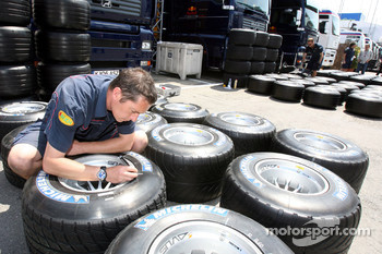 A Red Bull Racing crew member marking Michelin tires