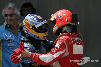 Race winner Fernando Alonso celebrates with Michael Schumacher