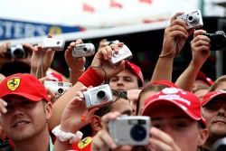 Fans take photographs in the pitlane