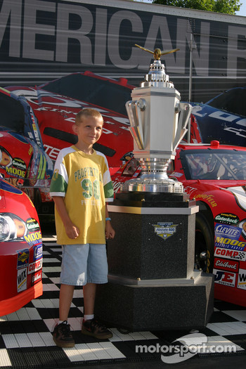 A young fan poses with the Allstate 400 at the Brickyard trophy