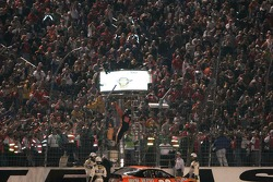 Tony Stewart climbs the fence after his victory