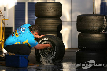 A Renault F1 Team mechanic cleans the Bridgestone tyres